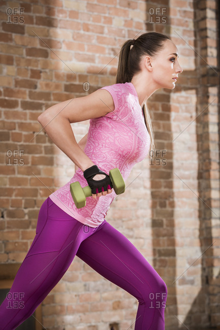 Side view of female athlete lifting dumbbell while standing against brick wall in gym