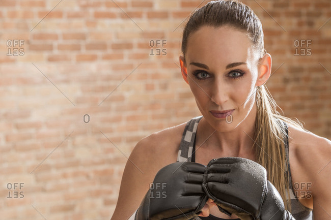 Portrait of confident female boxer practicing boxing while standing against brick wall in gym
