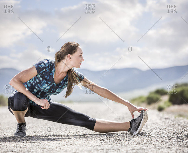 Full length of confident woman stretching leg while exercising on road against cloudy sky