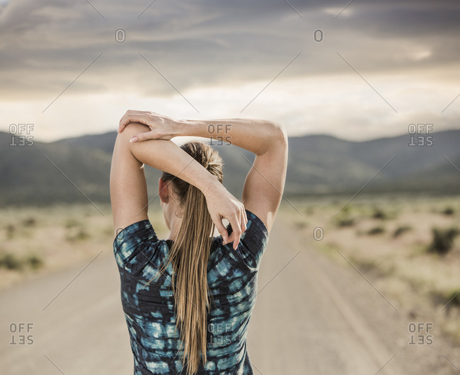 Rear view of woman stretching arms while standing on road against cloudy sky