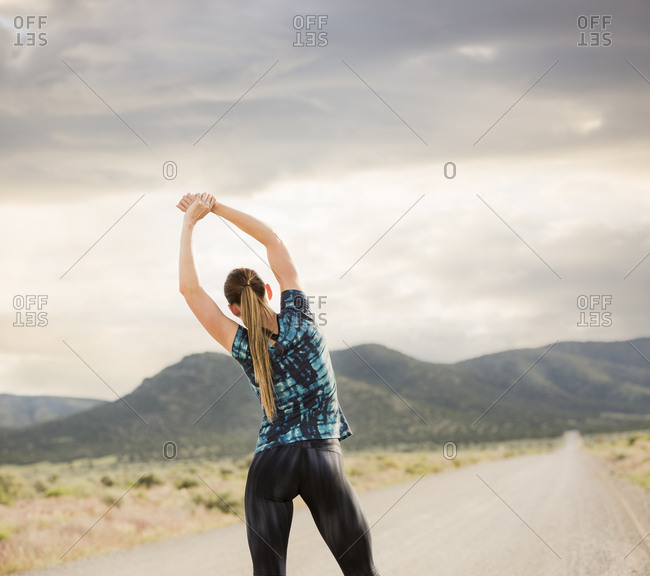 Rear view of woman stretching arms while exercising on road against cloudy sky
