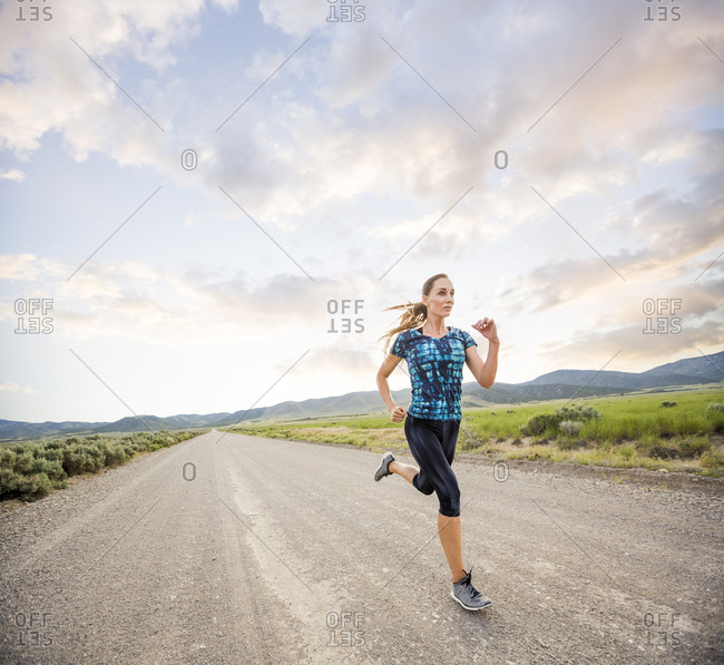 Full length of woman running on road against cloudy sky