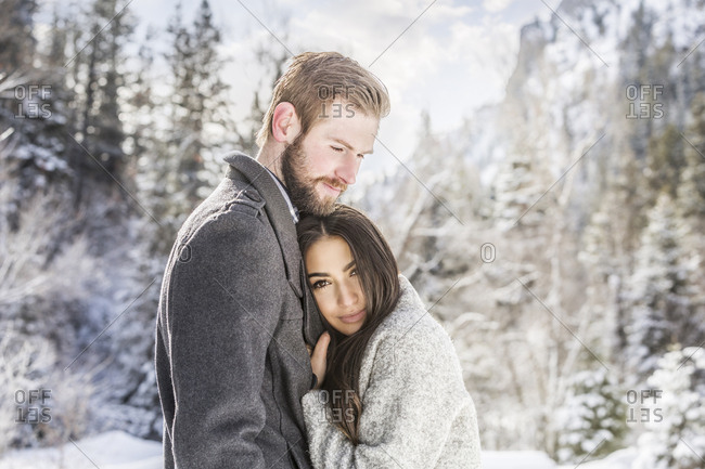 Portrait of wife embracing husband while standing in forest during winter