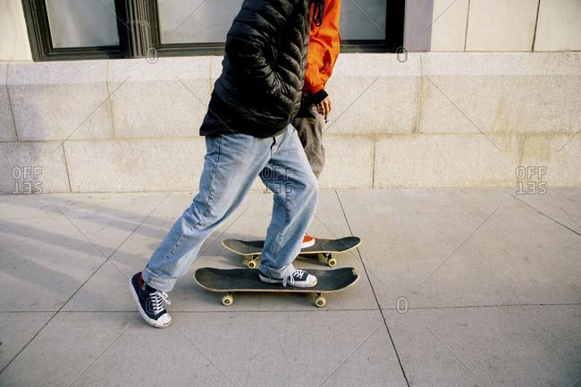 Low section of friends skateboarding on sidewalk in city