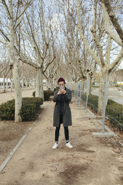 Man photographing with smart phone while standing on footpath amidst bare trees at park