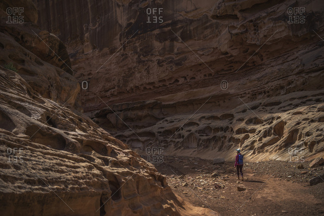 Rear view of female hiker with backpack walking amidst rocky mountains
