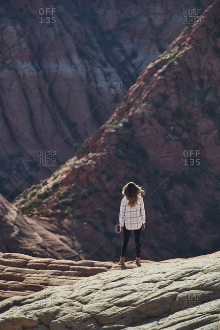 Rear view of female hiker standing on rock formation at Zion National Park during sunny day