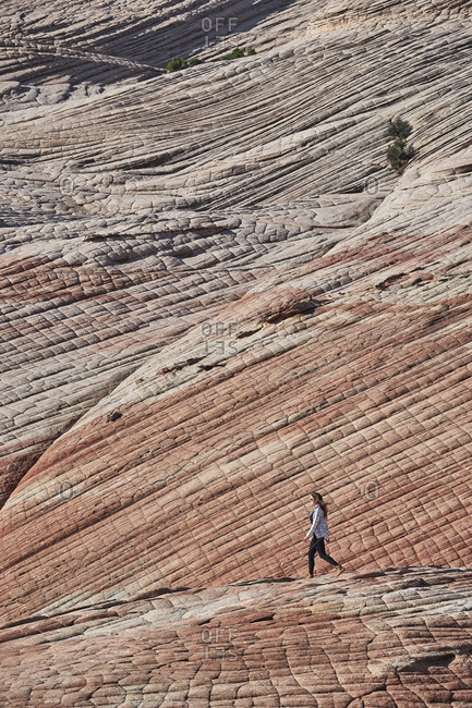Side view of female hiker walking on rock formation at Zion National Park during sunny day
