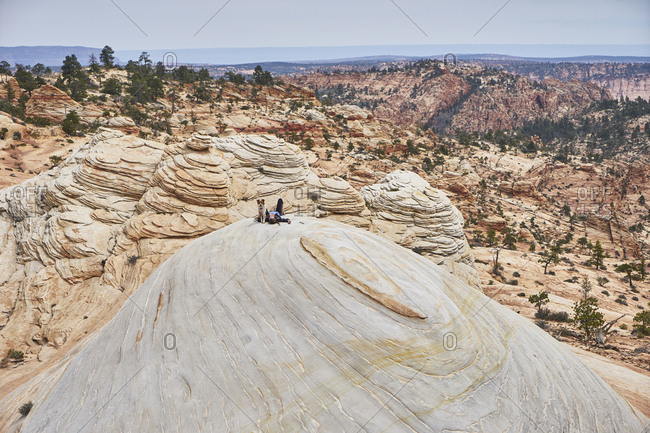 Female hiker with dog relaxing on rock formation against sky during sunny day