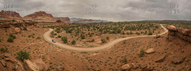 Aerial view of car on dirt road at desert