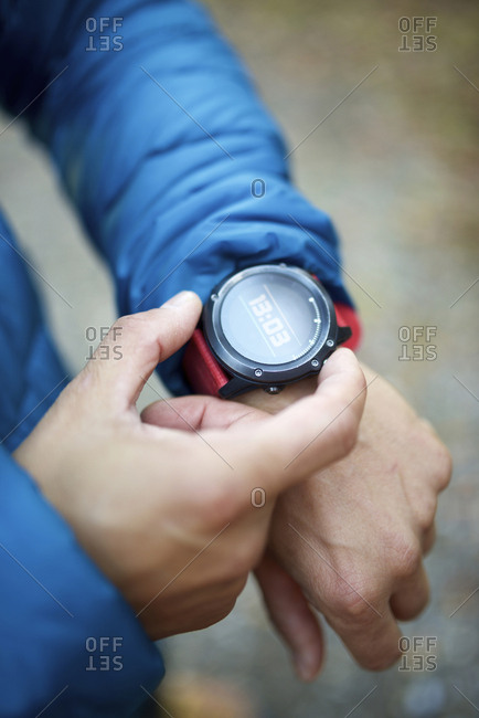 Midsection of man in warm clothing wearing smart watch while standing outdoors