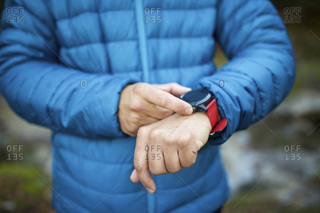 Midsection of man in warm clothing checking smart watch while standing outdoors