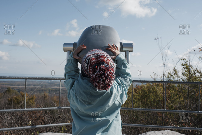 Rear view of girl in warm clothing looking through coin-operated binoculars against sky at observation point