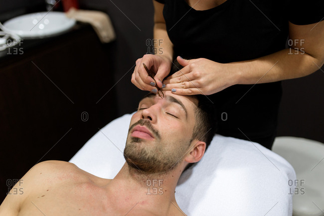 Relaxed young man is getting eyebrow waxing at beauty salon