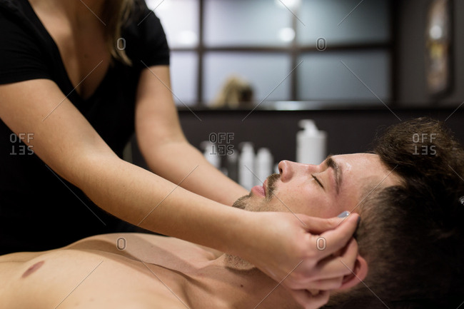Side view of young relaxed man is getting facial massage at beauty salon