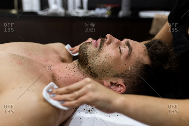 Side view of young relaxed man is getting a massage by a cosmetician