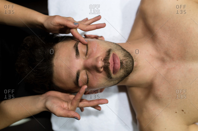 Overhead view of young man is getting facial massage by a cosmetician in a beauty spa
