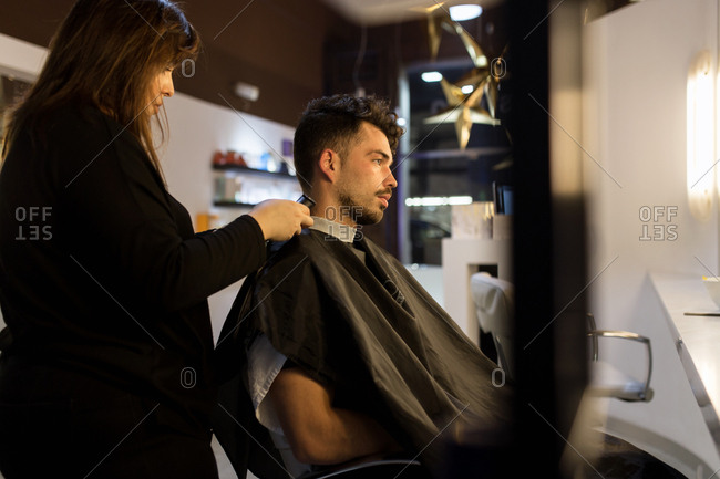 Hair dresser cutting hair of young caucasian man