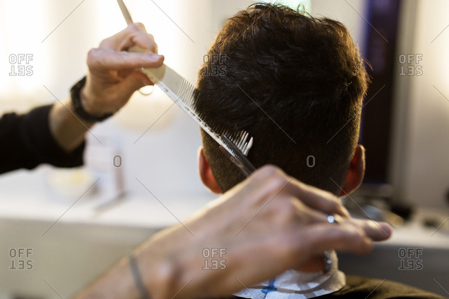 Detail of hairdresser hands cutting hair of young man