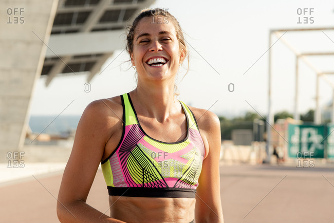 Young blonde runner woman smiling and looking at camera