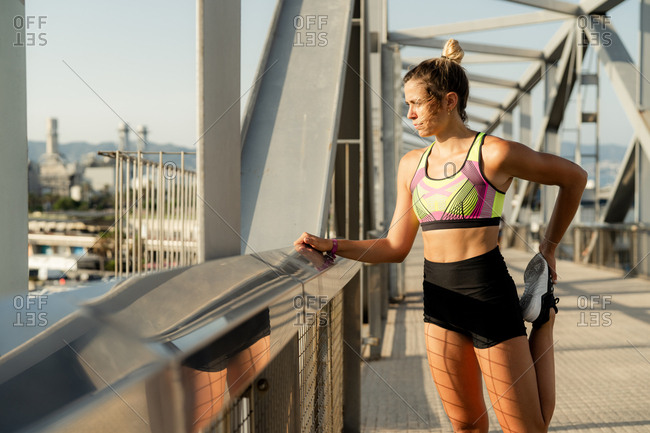 Young blonde woman doing stretches after workout in a sunset of summer