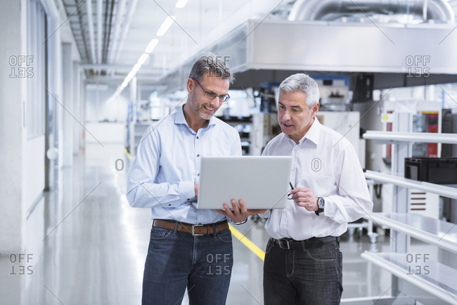 Two managers standing in company using laptop