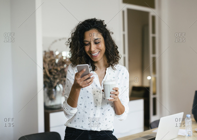 Businesswoman in office using smart phone- holding cup of coffee