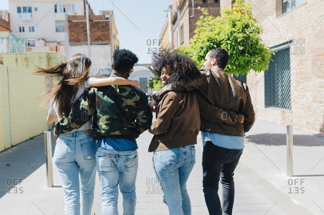 Rear view of stylish friends walking on urban street