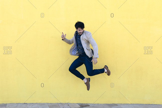 Young man jumping in the air in front of yellow wall