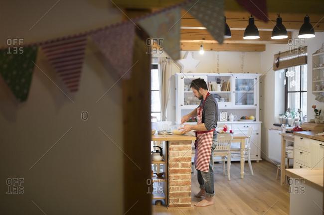Man standing in kitchen- preparing cake dough