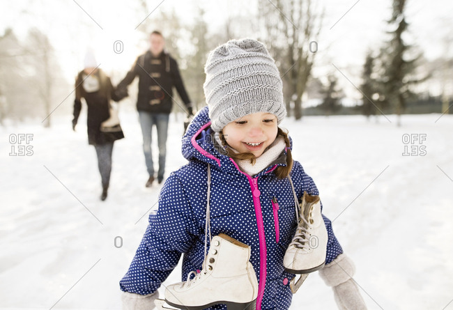 Little girl going ice skating with her parents