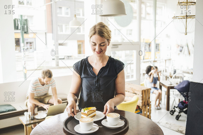 Waitress in a cafe serving cake and coffee