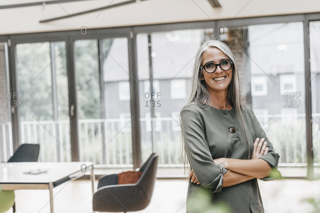 Portrait of smiling woman with long grey hair in office