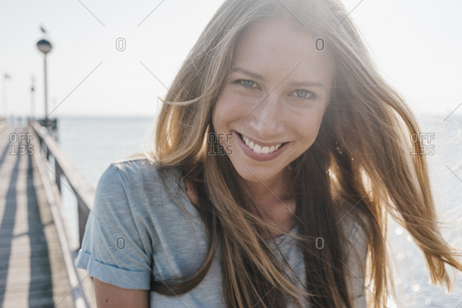 Portrait of happy young woman on jetty at backlight