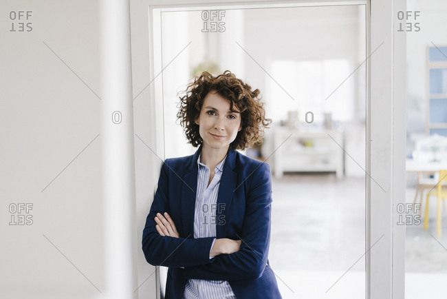 Businesswoman standing in her office with arms crossed