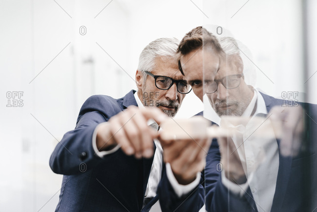Two businessmen examining architectural model at glass pane