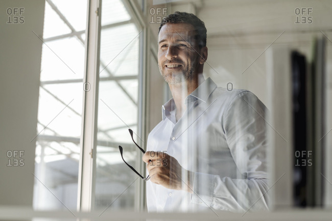 Smiling businessman holding glasses standing at the window