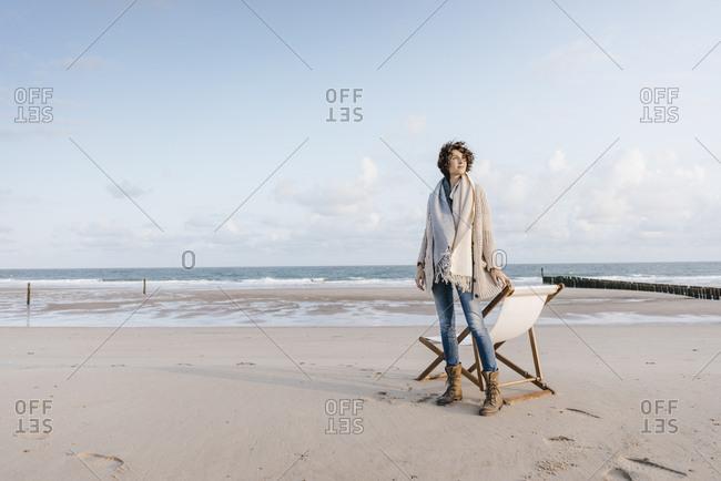 Woman standing next to deckchair on the beach