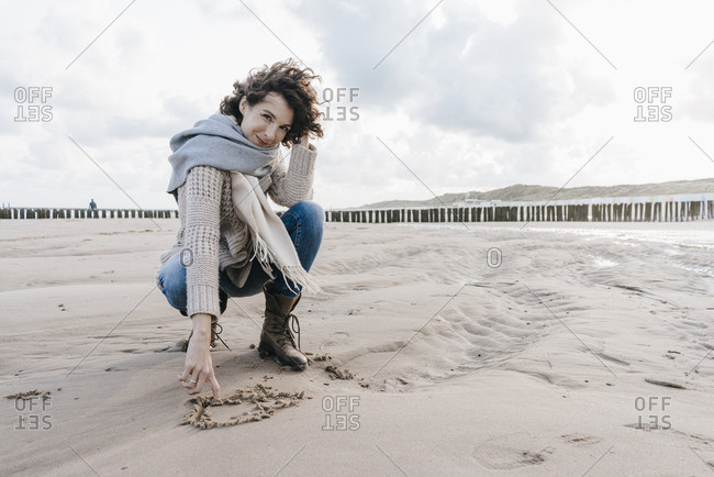 Woman crouching on the beach drawing a heart in the sand