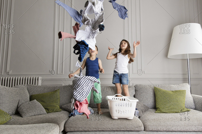 Siblings standing on the couch throwing laundry in the air