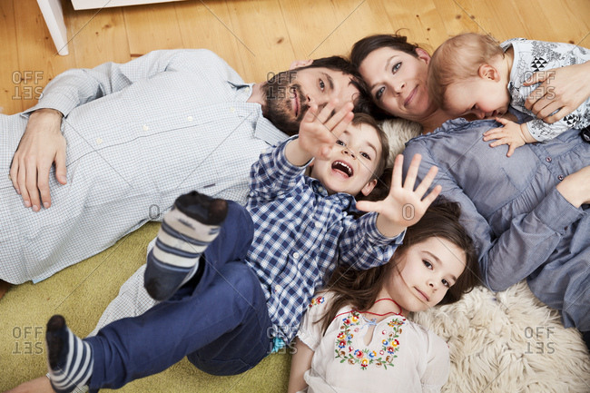 Family with three children lying on the floor at home looking at camera