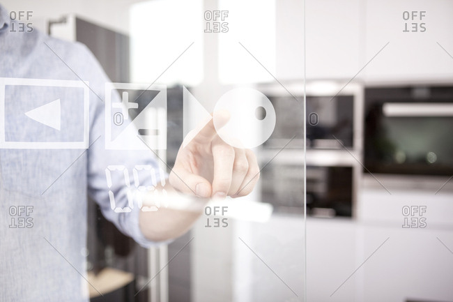 Man's hand using touchscreen of oven in his kitchen