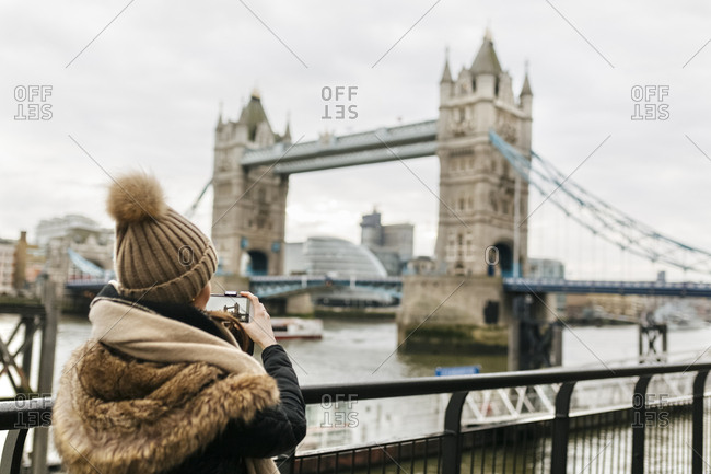 UK- London- back view of young woman taking picture of Tower of London