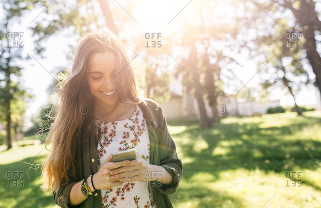 Young woman sending messages with her smartphone