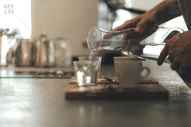 Man's hand pouring water into a glass in a coffee bar