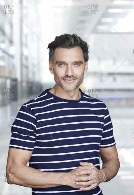 Portrait of smiling mature man with stubble wearing stripes t-shirt