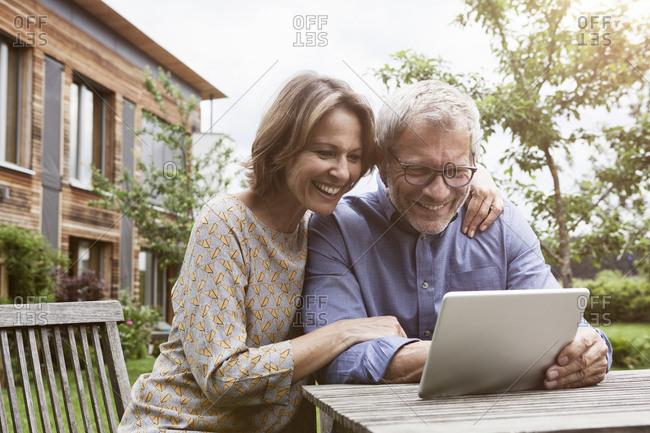 Happy mature couple sharing digital tablet in garden