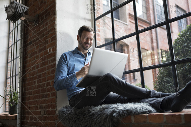 Mature man sitting on window sill- using laptop