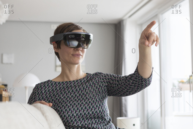 Woman at home using Augmented Reality Glasses at home