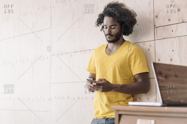 Young man leaning against wooden wall using cell phone